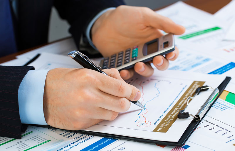 A businessman holds a calculator in one hand and traces a graph with his pen on the printout in front of him.