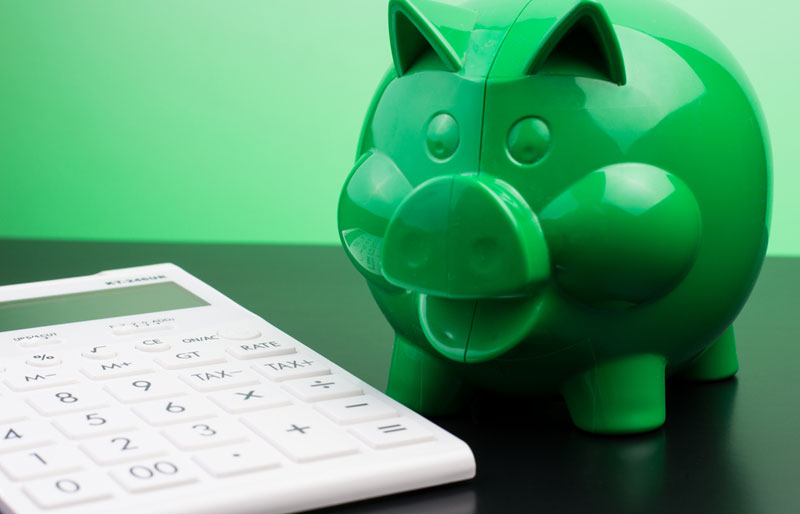 A calculator and a green piggy bank are on a table.