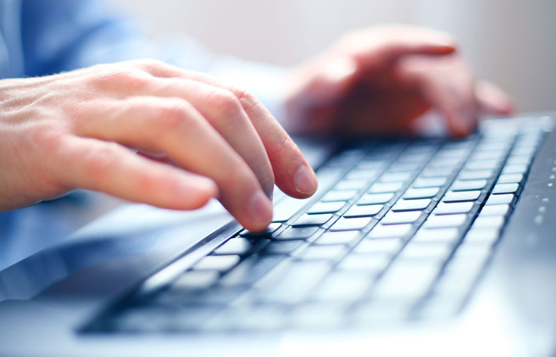 Close-up of a man's hands typing on a computer keyboard.