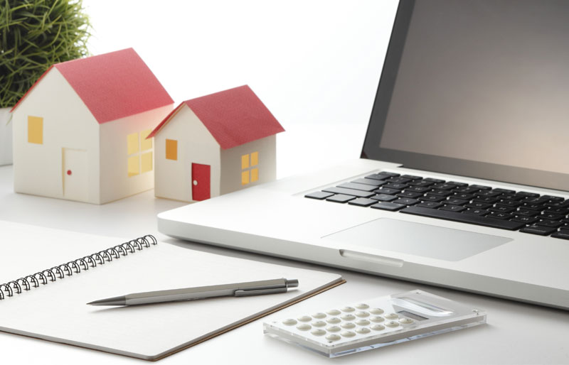 Two model houses, one small and one large, sit on a desk next to a laptop, calculator, pen and pad of paper.