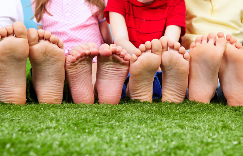 Close-up of a father, daughter, son and mother's bare feet as they are seen sitting side-by-side in the grass.