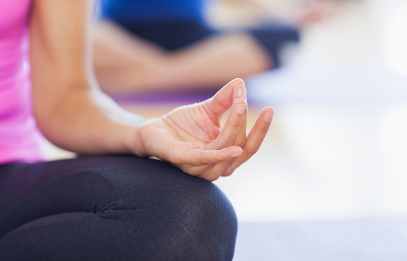 Close-up of a woman's hand as she is in the lotus position at a yoga class.