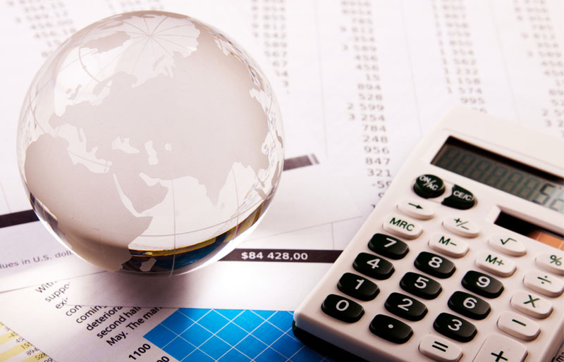 A glass globe paperweight and a calculator sit on an assortment of report printouts.