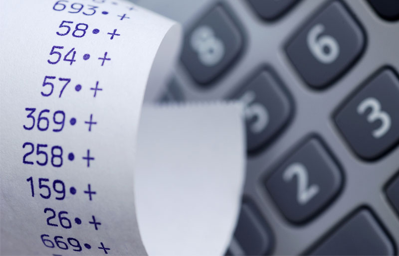 Close-up of a calculator printout showing a series of additions. A calculator is in the background.