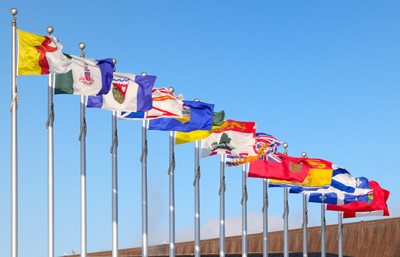 Flags of the Canadian provinces and territories are seen flying in the wind atop a series of flagpoles under a blue sky.