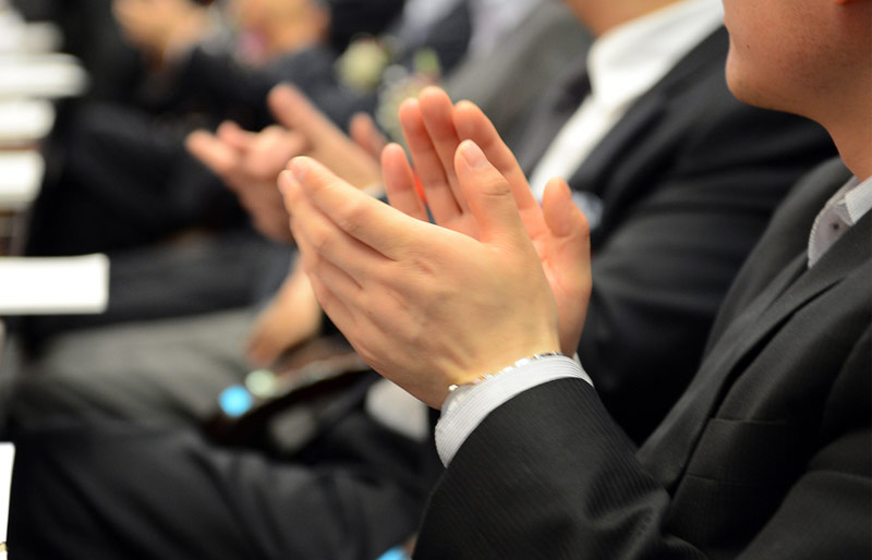 A close-up of a businessman's hands clapping. He is part of a larger audience of businesspeople.