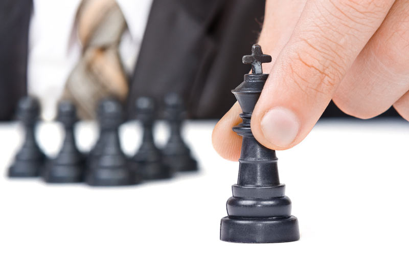 A businessman holds the figure of a black king from a chess set while six pawns are gathered in the background.