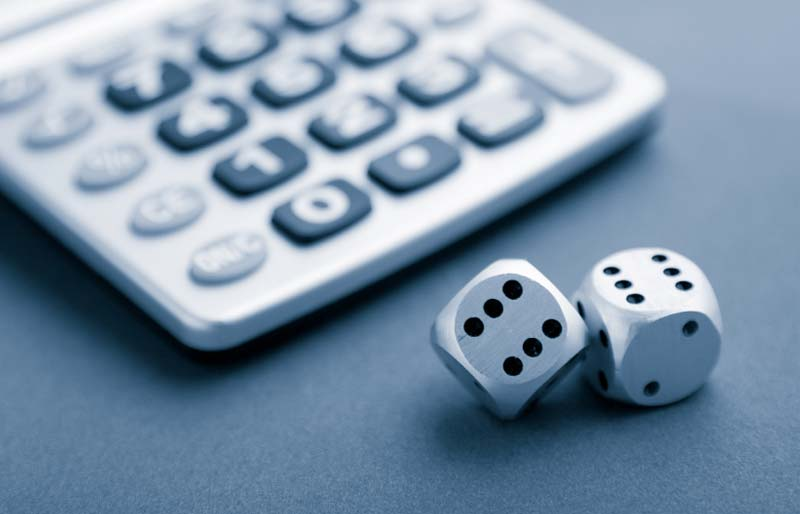 A pair of dice, one showing six and the other tipped on its edge but also showing six, sit in front of a calculator.