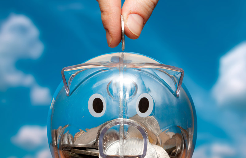 A hand drops a coin into a transparent piggy bank that appears half full.
