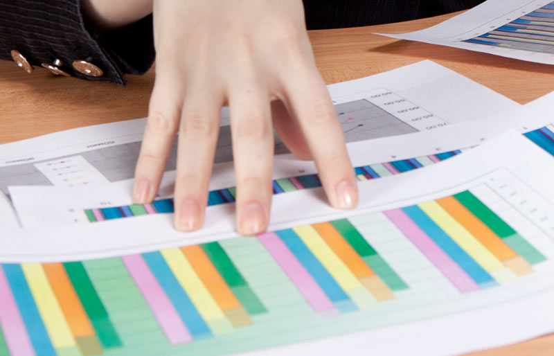 A close-up image of a persons fingers holding down a spreadsheet on a desk.
