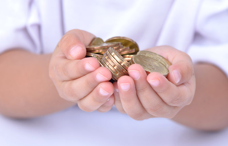A close-up photograph of a pair of hands holding large gold coins.