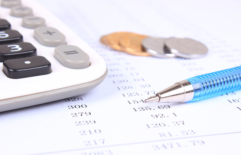 A close-up of a calculator, coins, a pen and a spreadsheet.