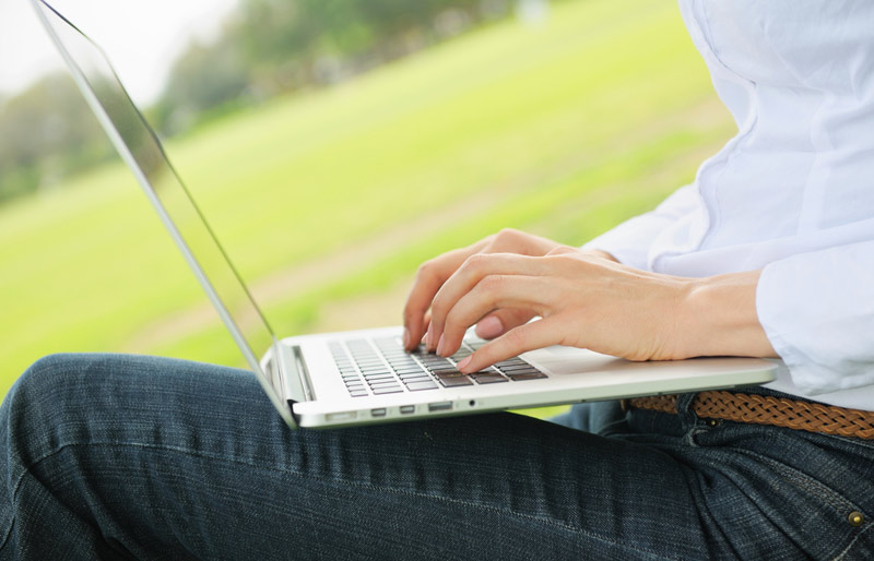 A woman wearing jeans and a white shirt types on a laptop outdoors in a park setting.
