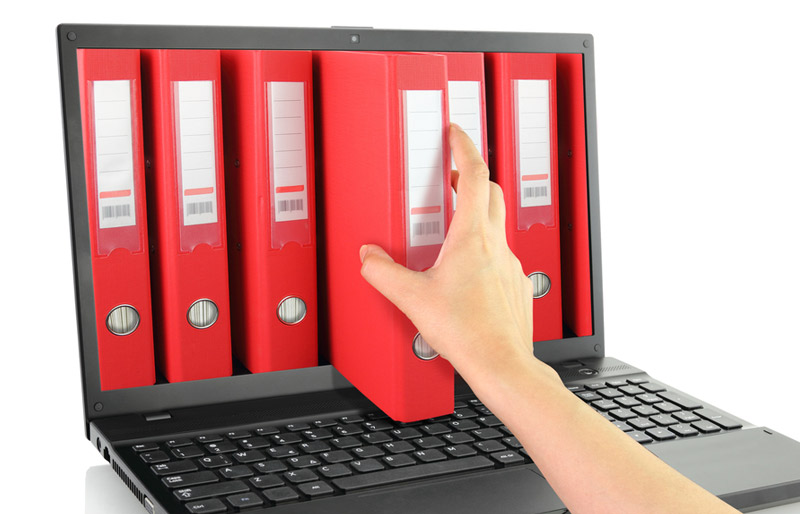 A woman's hand is pulling a red loose leaf binder from a shelf of similar binders that appear to be arranged in a row on the screen of a laptop computer.