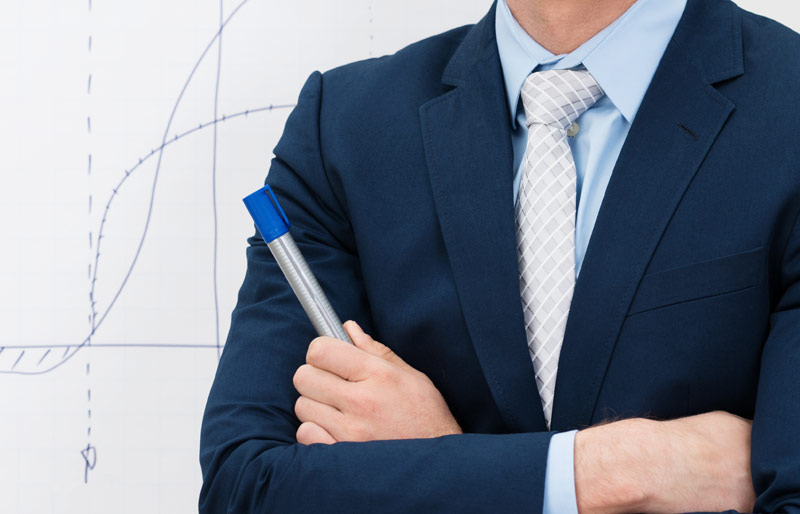 A businessman with arms crossed holds a marker. He is standing in front of a whiteboard on which is drawn a graph.