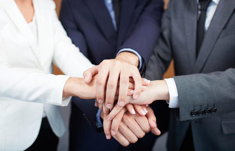 Business people put their hands one atop the other to form a team huddle.