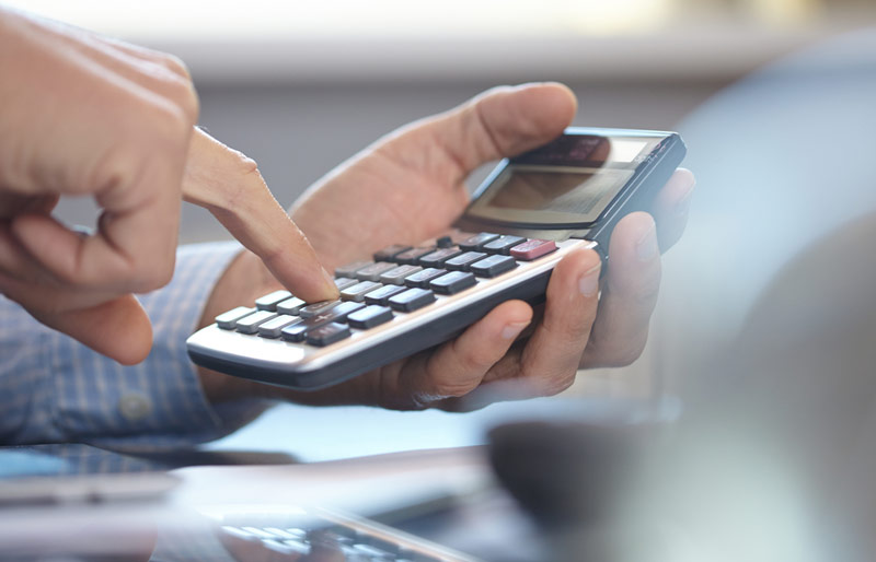 A close-up of a business professional using a hand held calculator.