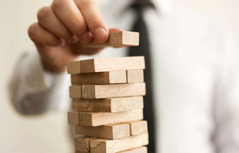Business man placing top block on Jenga game stack