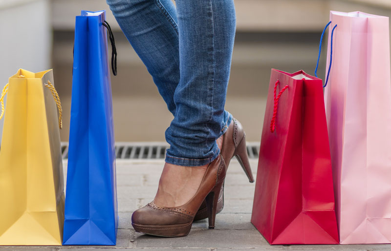 Close up of shopping bags on ground next to woman's feet