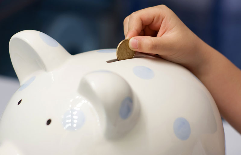 Child putting coin into piggy bank