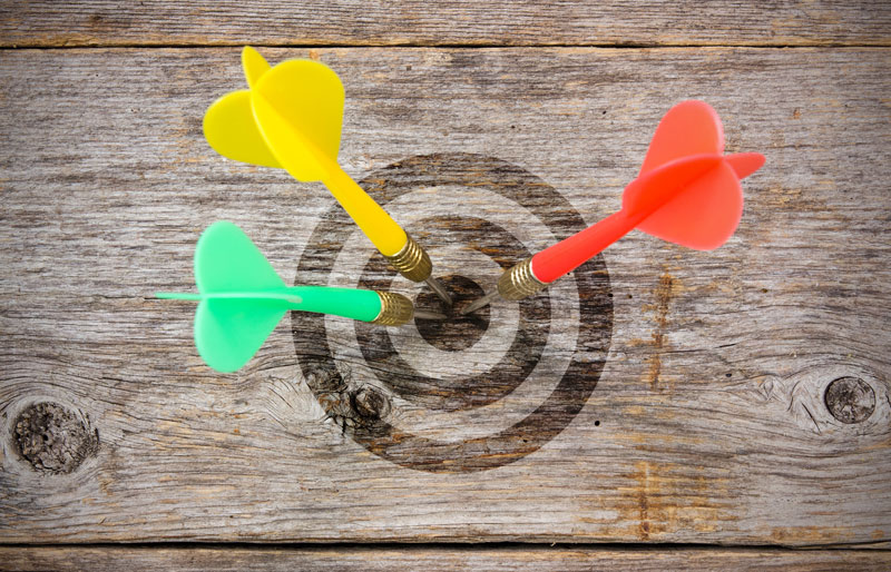 Colourful darts hitting bulls-eye of target on wooden background