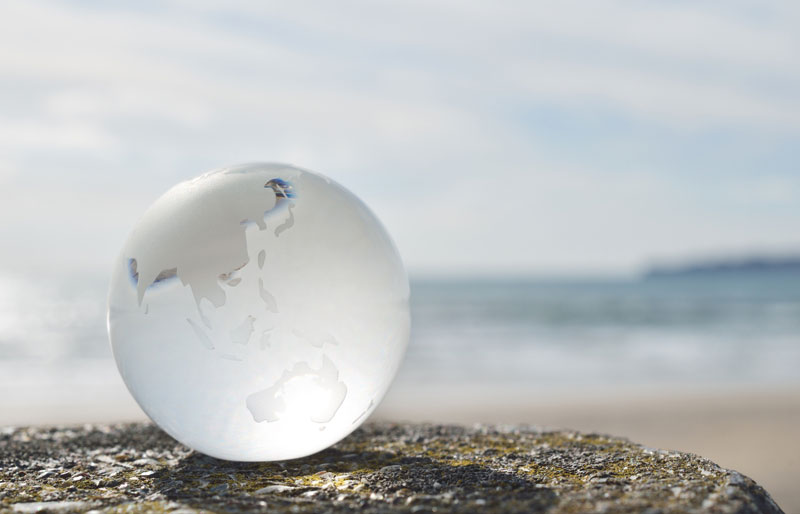 Globe sitting on cement wall by the ocean beach