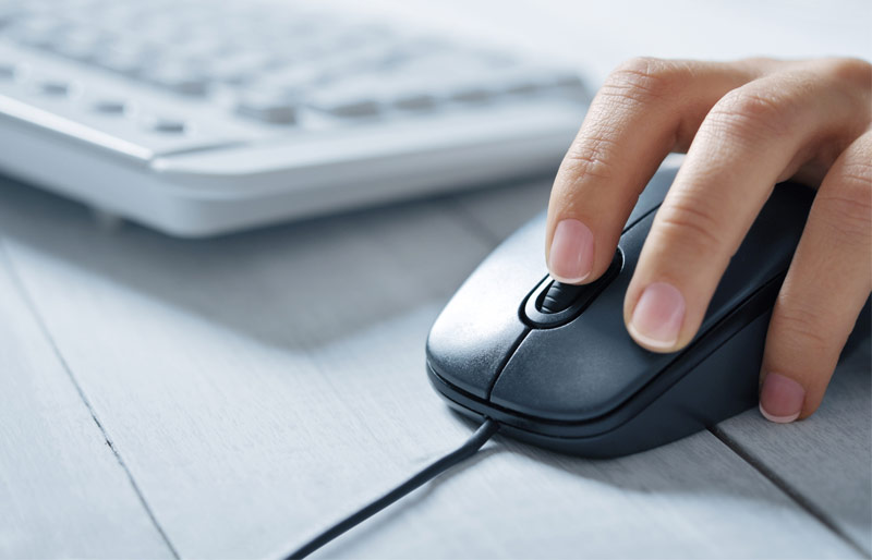 Person using mouse on desk next to computer keyboard