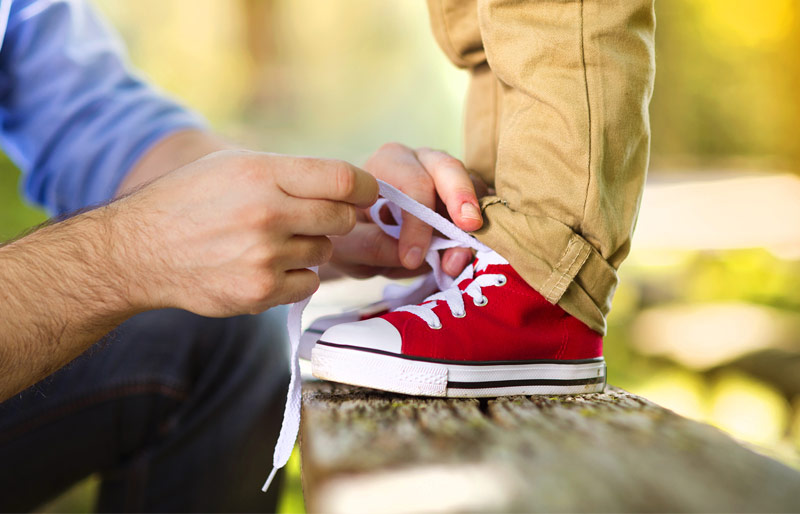 Father tying shoes of child standing on park bench