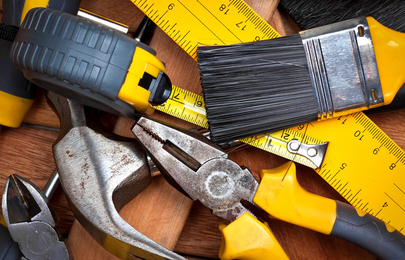 Pile of construction tools on wooden table