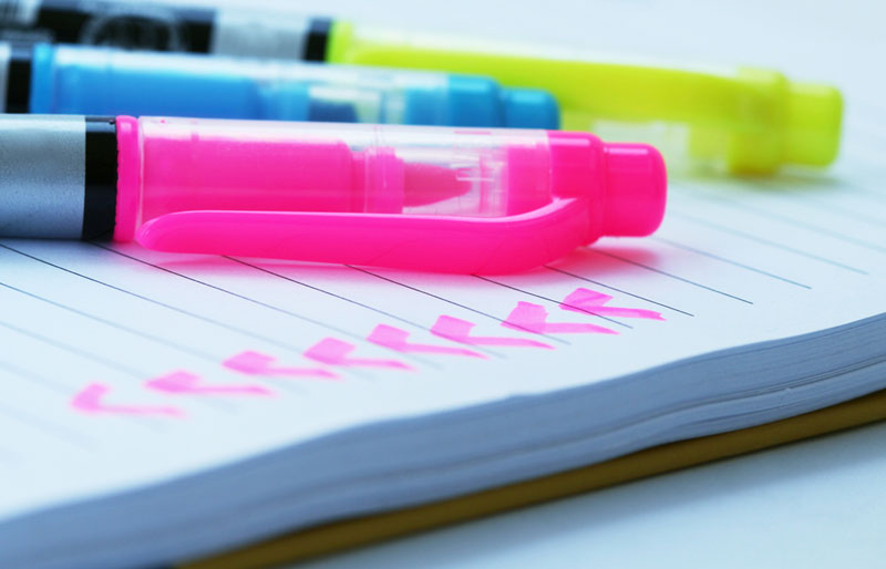 This is a photograph of various coloured markers on a notepad.