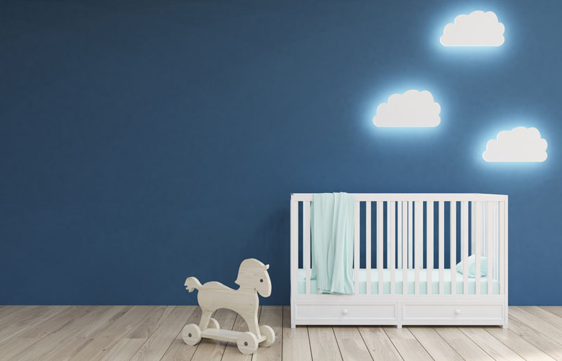 room interior with a crib, cloud shaped lamps and a toy horse
