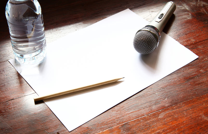 microphone with paper on a brown wooden desk
