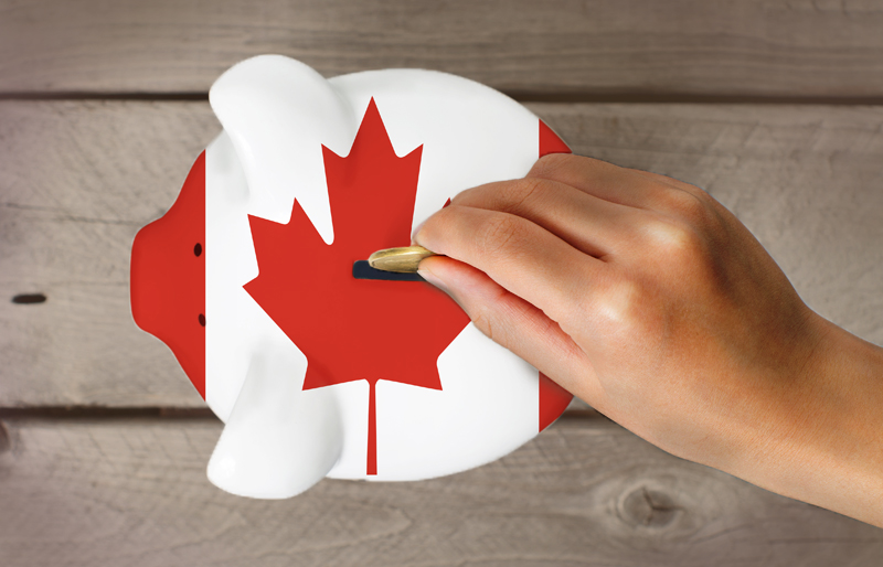 Hand dropping coin in to piggy bank painted as the Canadian flag