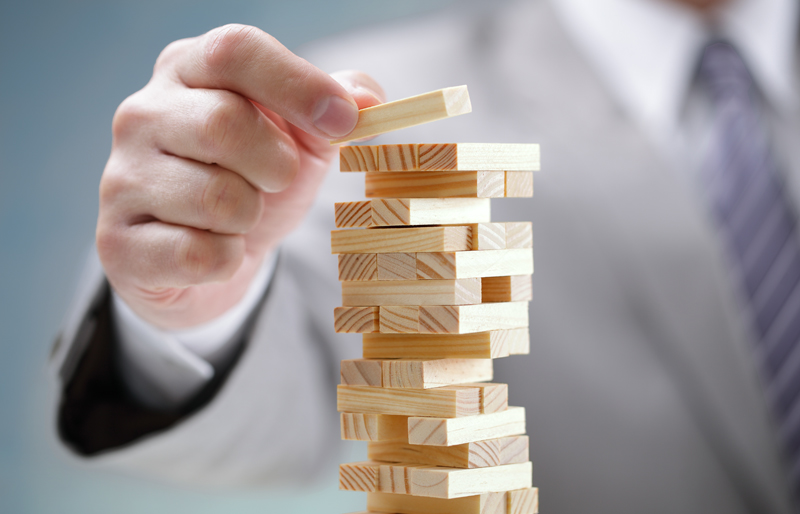 Hand of businessman balance small wood block on top of other stacked wooden blocks