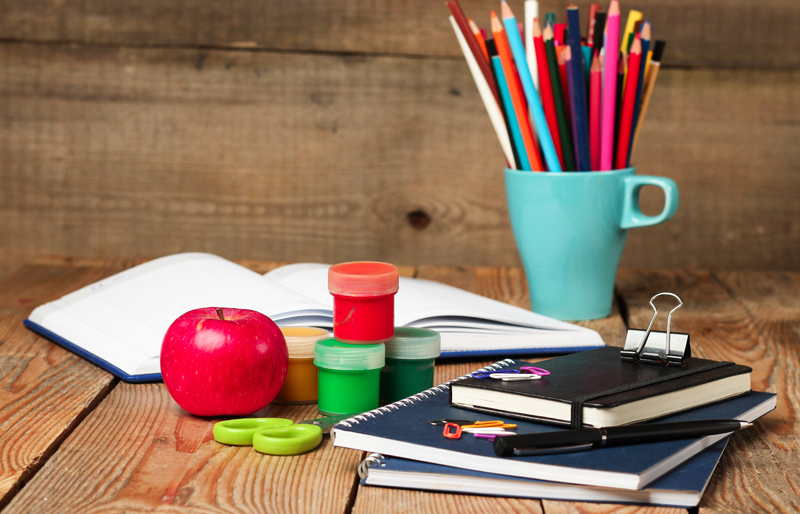 School materials on a desk, with a cup of colour pencils and an apple