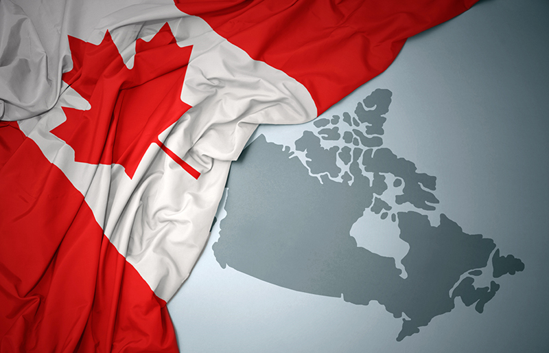 Canadian flag draped over a map of Canada