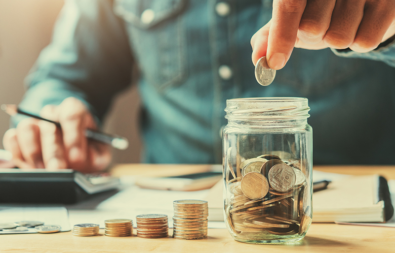 person using calculator, dropping coin in to a glass jar with other coins, with other coins stack resembling a bar chart