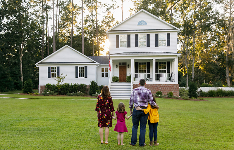 Family of four standing in front of a big two-story house surrounded by trees