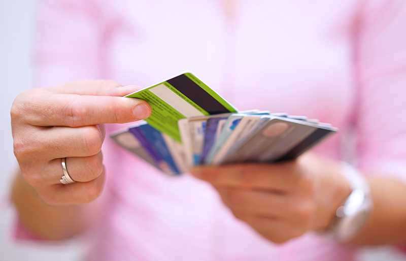 Young woman holding several credit cards in her hand, and selecting one