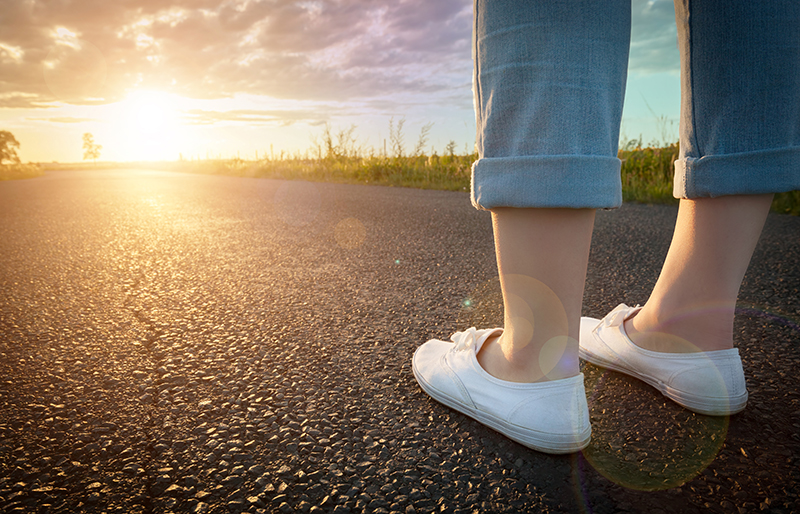 feet of a person standing on a road, facing the sun setting at end of the road