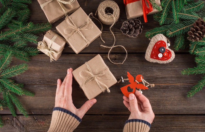 Hands holding a box with a gift on a wooden background.