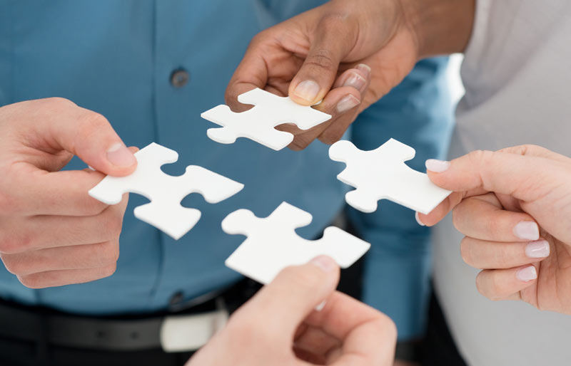 Business people holding puzzle pieces to put together