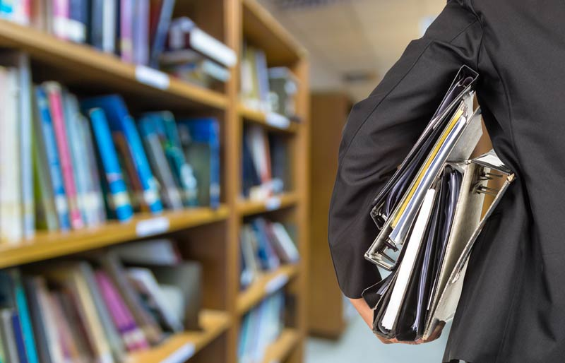 A close-up of a business professional holding a stack of binders and standing in a library.