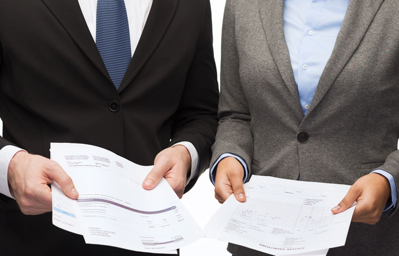 A picture of two business professionals holding various reports.