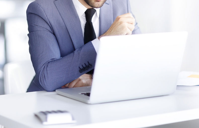 Business man in blue suit concentrating on laptop with calculator
