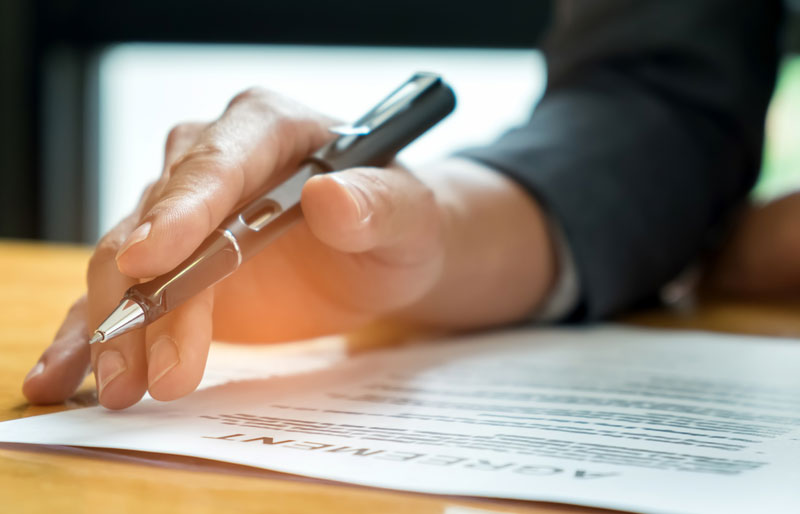 Business hand holding a pen on top of an agreement paper