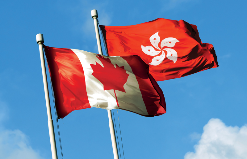 Photo of both the Hong Kong flag and Canadian flag  blowing in the breeze side-by-side