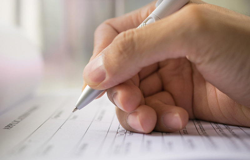 Close of a person's hand using a pen to fill out a form.
