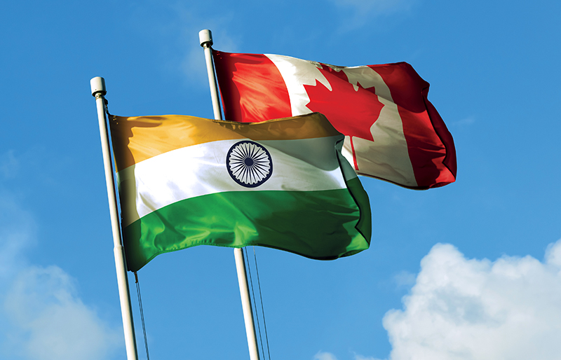 Flags for both India and Canada waving together in the breeze against a blue sky