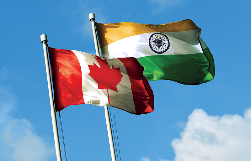 Flags for both Canada and India waving together in the breeze against a blue sky
